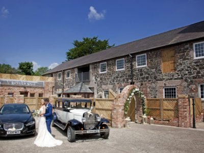 stone walled wedding venue with cars